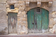 Big and small old gates. Street of an old fisher village at the island Malta, Marsaxlokk. Old green big gate with an arch and small traditional. Building made of Royalty Free Stock Photo