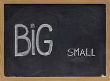 Big and small - opposite or contrast concept. Words big and small handwritten with white chalk on blackboard, contrast, opposition or contradiction concept stock image