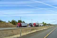 Big and small rigs semi trucks convoy running on divided highway with another traffic. Big and small industrial rigs long haul and local delivery semi trucks royalty free stock images