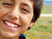 BIG Smile. Boy smiling with poppy field in background stock photo