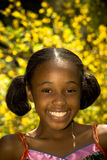 Big Smile Against Bright Flowers. A young african american girl with a big smile against beautiful yellow flowers Stock Images