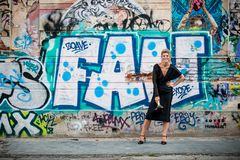 Big smile of an elegant lady in front of a wall with graffiti. A wall vandalized with street graffiti art. stock image