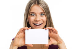 Big smile, fun and white card. Close up portrait of a young woman showing a blank signboard, on white Stock Photo