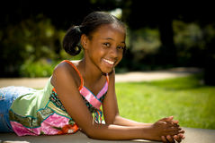 Big Smile While Relaxing. A young african american girl with a big smile while relaxing in the sun Royalty Free Stock Photos