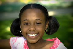 Big Smile In The Shade. A young african american girl is happy and content Stock Images