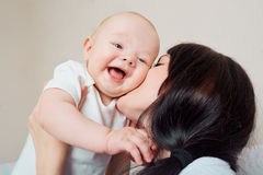 Big smile toddler. Mom hugging baby. Kid laughing in the arms of Stock Photography