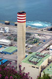 Big smokestack of factory near sea Stock Images