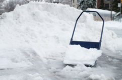Big snow shovel full of heavy icy snow Stock Photos