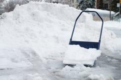 Big snow shovel full of heavy icy snow Stock Photos