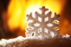 Big snowflake toy in snowdrift on hill Royalty Free Stock Images