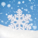 Big snowflake toy with snowfall on sky background Stock Photos