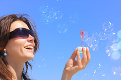 Big soap bubble. Young Girl blowing soap bubbles with blue sky Royalty Free Stock Images