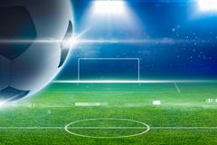 Big soccer ball above green stadium with bright spotlights Stock Images