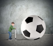 Big soccerball. Baby boy amused swollen a big soccer ball stock images