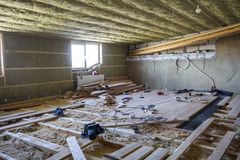 Big spacious light empty attic room under construction and renov. Ation. Mansard floor and ceiling insulation with rock wool. Fiberglass insulation staff in Stock Images