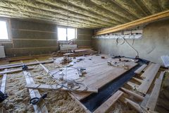 Big spacious light empty attic room under construction and renov. Ation. Mansard floor and ceiling insulation with rock wool. Fiberglass insulation staff in Royalty Free Stock Image