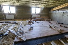 Big spacious light empty attic room under construction and renov. Ation. Mansard floor and ceiling insulation with rock wool. Fiberglass insulation staff in Stock Photography