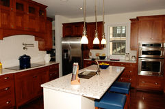 Big spacy kitchen in a new house. A beautiful kitchen with nice woodwork and appliance and a centre sink Stock Images