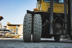 Big spiked wheels of yellow tractor durable rubber tires. Background business car pattern texture construction vehicle equipment heavy industry large stock photo