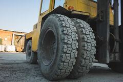 Big spiked wheels of yellow tractor durable rubber tires. Background business car pattern texture construction vehicle equipment heavy industry large royalty free stock photo