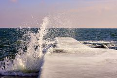 Big splash of cold water hits pier. In the ice on the northern coast of the Black Sea. Odessa, Ukraine Stock Photos