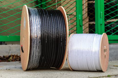 Big spool of optic wires. Two big spools of optic wire standing on the ground in the factory Stock Photo