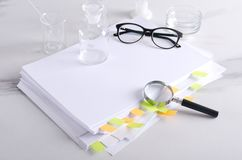 Big stack of books and professional stethoscope on it.Concept of big data in medicine. Magnifier against stack of documents, medical glassware, glasses on the royalty free stock image
