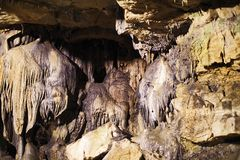 a big stalactite is hanging from the rock royalty free stock photo