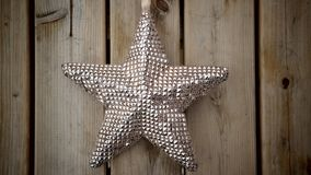 A big star. A star hangs in the middle, with wooden background Royalty Free Stock Photos