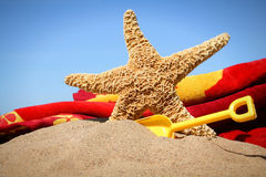 Big starfish in the sand. With shovel and beach towel Royalty Free Stock Image
