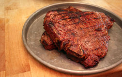 Big Steak. A big juicy steak sits on a platter ready to eat Stock Image