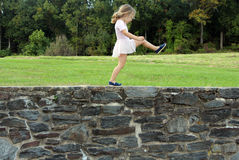 Big Steps. Girl playing on a stone wall Stock Photos