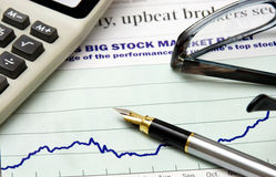 Big stock market. Gold fountain pen, eyeglasses and calculator on the graph Royalty Free Stock Image