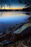 Big stone on the bank of deep blue lake. Stock Photos