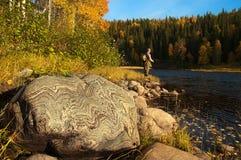 A big stone with beautiful pattern. Fisherman on Stock Photos