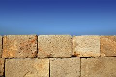 Big stone bricks masonry wall on port blue sky Stock Photos