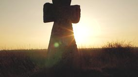 Big stone cross in a field at sunset in the rays of the sun.  stock video footage