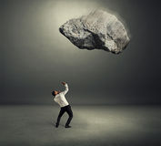 Big stone falling down on scared businessman Royalty Free Stock Photo