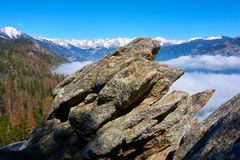 Big stone in foreground of a mountain landscape with clouds in the valley. Moro Rock, Sequoia National Park, California, USA royalty free stock image