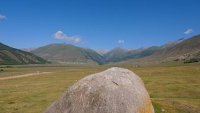 Big stone in green meadow in highlands landscape and mountain peaks on blue sky. Summer fields and hills in mountain valley stock video