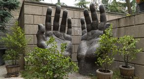 Stone sculpture big hands to the sky stock photos