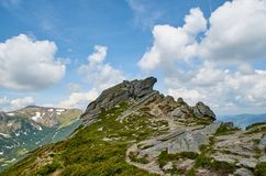 Big stone scaur in Carpathian mountains with the blue sky and white clouds. In the summer stock photos