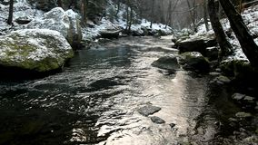 Big stone with small icicles in cold milky blurred water of mountain stream. Royalty Free Stock Images
