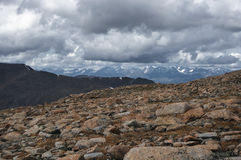Big stones on the background of high mountain snow peaks ranges under cloudy gloom dark sky Stock Photography