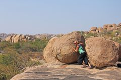 Big stones in Hampi, Karnataka, India. The man pushes the stone.  stock photos