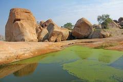 Big stones and a lake in Hampi, India.  royalty free stock image