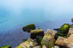 Big stones on seashore, blue water Stock Images