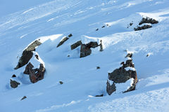 Big stones on snowy slope. Royalty Free Stock Images