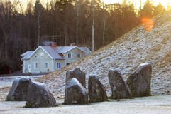 The big stones standing in the snow field in winter Stock Images