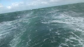 Big storm waves in the ocean. View from the stern of the sailboat